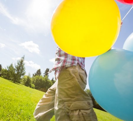 Boy With Balloons Walking In Meadow