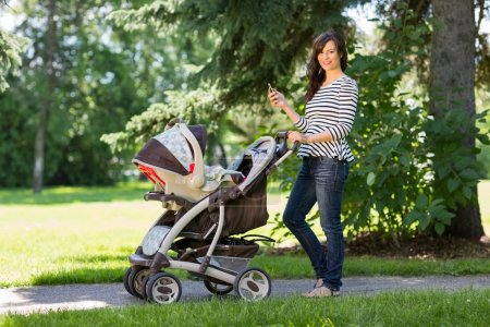 Mother With Cell Phone And Carriage Walking In Park