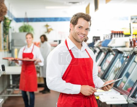 Photo for Portrait of happy butcher holding digital tablet at store with colleagues working in background - Royalty Free Image