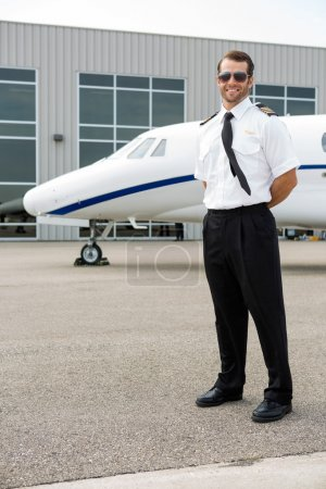 Confident Pilot With Private Jet In Background