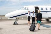Geschäftsfrau mit Gepäck zu Fuß in Richtung Privatjet