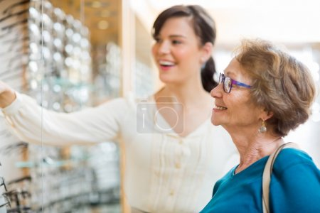 Photo for Young woman assisting senior female customer in selecting glasses at store - Royalty Free Image