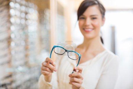 Photo pour Portrait de jeune femme heureuse montrant des lunettes au magasin - image libre de droit
