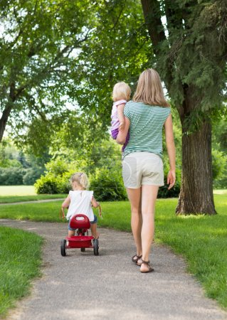 Photo for Full length rear view of mid adult mother with children strolling in park - Royalty Free Image