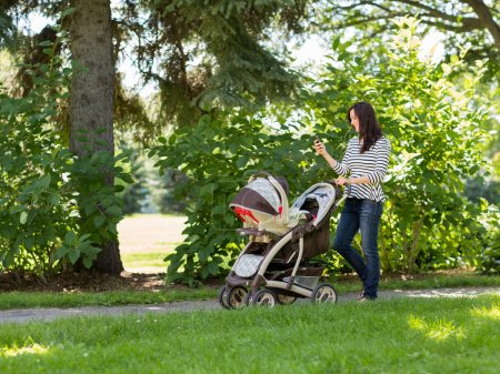 Woman With Baby Carriage Using Cell Phone In Park