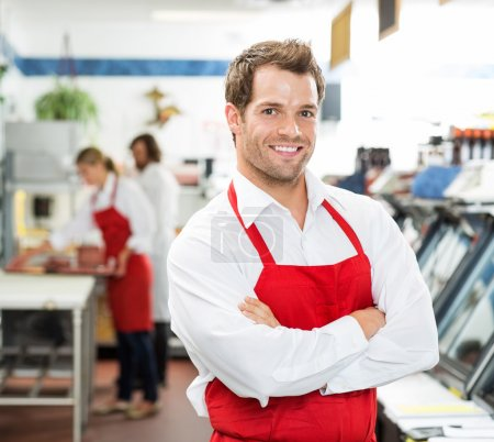 Confident Male Butcher Standing Arms Crossed At Store