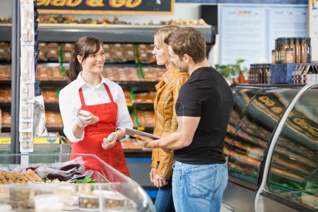 Saleswoman Assisting Couple In Buying Meat