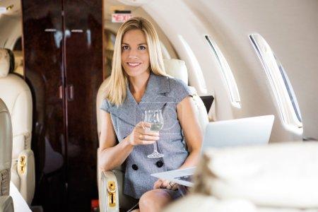 Photo pour Portrait de belle femme d'affaires ayant du vin en jet d'entreprise - image libre de droit