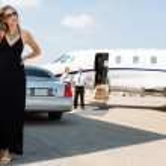 Full length of wealthy woman in elegant dress stan...