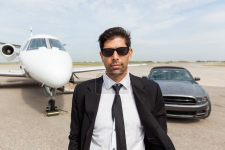 Entrepreneur In Front Of Car And Private Jet