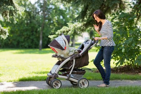 Woman Looking Into Baby Carriage In Park
