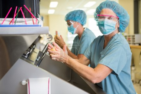 Doctor Scrubbing Hands With Colleague