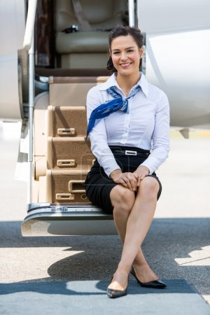 Stewardess Sitting On Ladder Of Private Jet