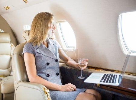 Photo pour Heureuse femme d'affaires tenant du verre à vin tout en regardant par la fenêtre de jet privé - image libre de droit