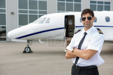 Pilot With Arms Crossed Standing In Front Of Private Jet