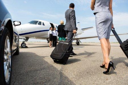 Photo pour Partenaires d'affaires avec bagages marchant vers le jet privé au terminal - image libre de droit