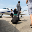 Business partners with luggage walking towards pri...