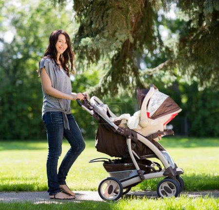Beautiful Woman Pushing Baby Carriage In Park