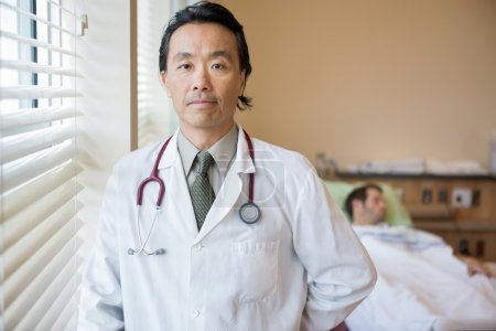 Confident Doctor With Patient In Background At Hospital Room