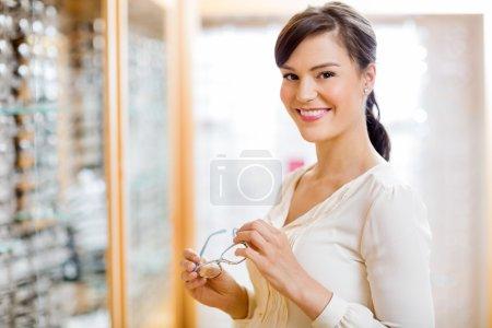 Photo pour Portrait de jeune femme heureuse achetant des lunettes dans un magasin d'opticien - image libre de droit