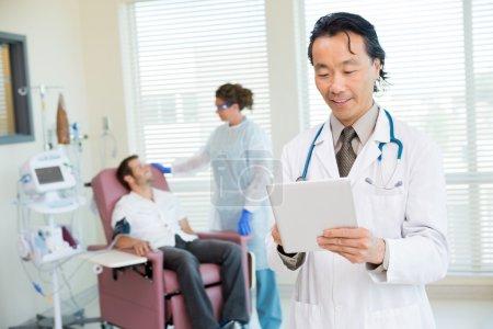 Doctor Using Digital Tablet In Chemo Room