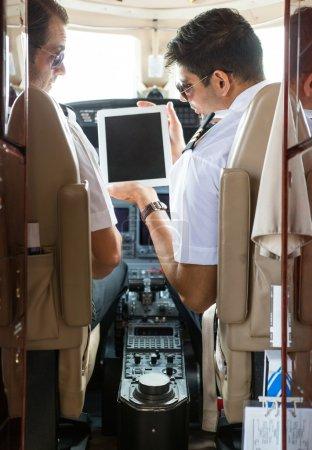 Pilot Showing Digital Tablet To Copilot In Cockpit