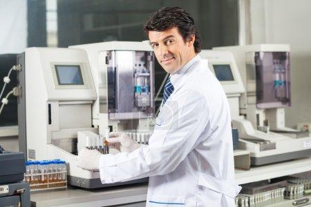 Scientist Using Urine Analyzer To Test Samples