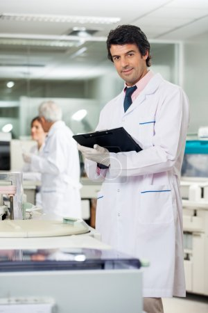 Scientist With Clipboard In Laboratory