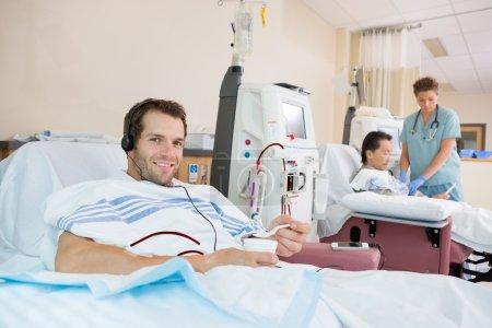 Photo pour Portrait d'un jeune patient dialysé tenant un verre de glace concassée pendant une dialyse rénale à l'hôpital - image libre de droit