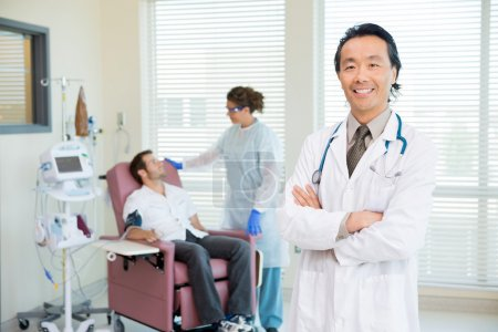 Happy Doctor With Patient Being Examined By Heartbeat Machine