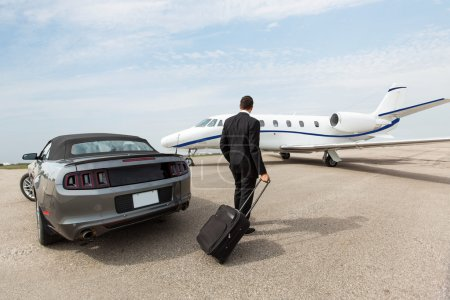 Businessman Standing By Car And Private Jet At Terminal
