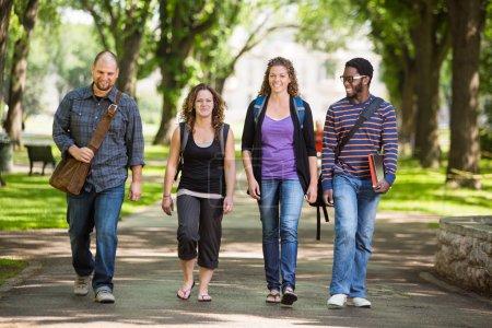 Photo pour Toute la longueur du multiethnique étudiants marchant sur la route des campus - image libre de droit