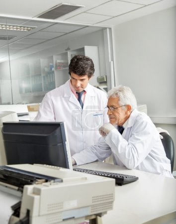 Photo for Male technicians discussing over computer in laboratory - Royalty Free Image