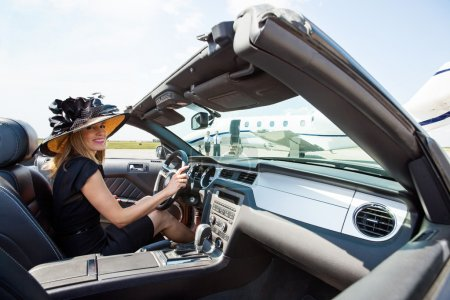 Woman Driving Convertible Towards Private Jet At Terminal