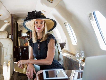 Photo pour Portrait de femme riche confiante assise dans un jet privé - image libre de droit