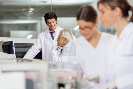 Photo for Male technicians discussing in lab with female colleagues working in foreground - Royalty Free Image