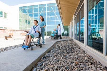 Medical Team With Patients On Wheelchairs At Hospital Courtyard