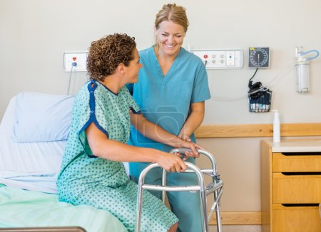 Nurse Assisting Patient Using Walking Frame In Hospital