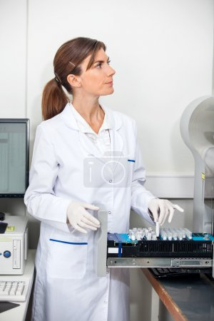 Researcher Loading Samples In Coagulation Analyzer