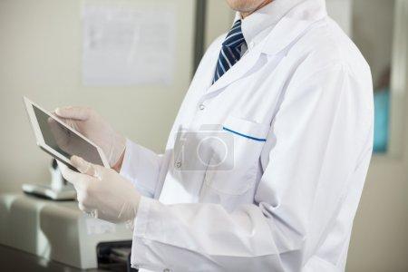 Photo pour Abdomen du mâle scientifique à l'aide de tablette numérique en laboratoire - image libre de droit