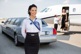 Attractive Airhostess Standing Against Limousine And Private Jet