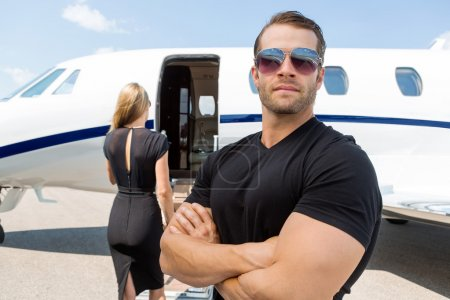 Bodyguard Standing Against Woman And Private Jet