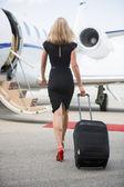 Zadní pohled na ženy se zavazadly pěšky směrem k soukromé letadlo