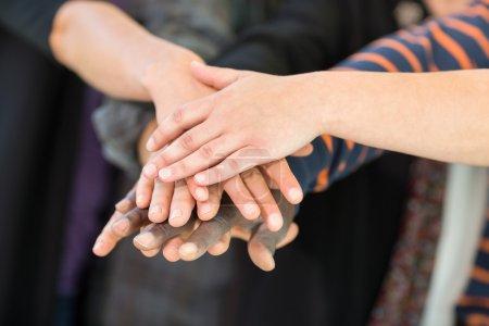 Photo pour Image recadrée d'étudiants universitaires multiethniques empilant les mains - image libre de droit