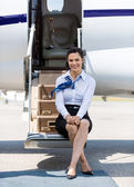 Air Hostess Sitting On Ladder Of Private Jet