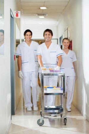 Technicians With Medical Cart Walking In Corridor