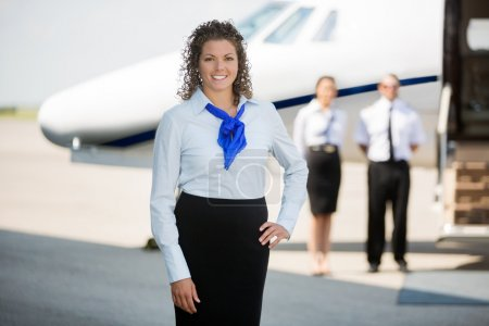 Airhostess With Hand On Hip Standing At Airport Terminal