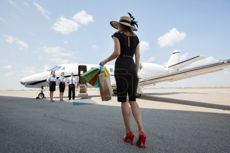 Woman Carrying Shopping Bags While Walking Towards Private Jet