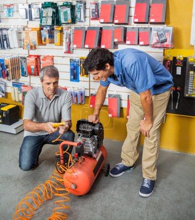 Photo pour Père et fils, examinant le compresseur d'air en quincaillerie - image libre de droit