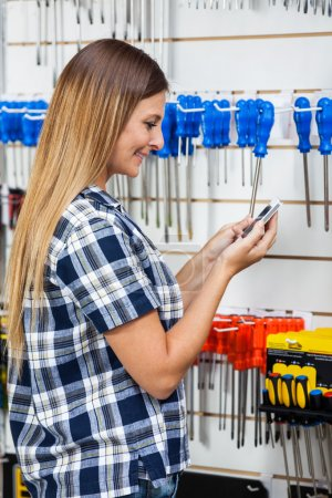 Woman Checking Information Of Screwdriver On Mobilephone